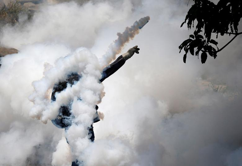 """A demonstrator throws back a tear gas grenade while clashing with riot police during the so-called """"mother of all marches"""" against Venezuela&squot;s President Nicolas Maduro in Caracas, Venezuela. REUTERS/Carlos Garcia Rawlins"""