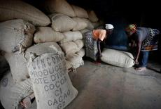 Women from a local cocoa farmers association lift a sack in a cocoa warehouse in Djangobo, Ivory Coast, November 17, 2014.   REUTERS/Thierry Gouegnon/File Photo -