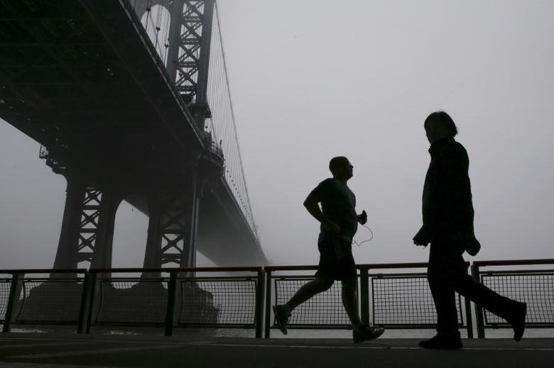 People are seen in silhouette exercising under the fog covered Manhattan Bridge in New York December 14, 2015.   REUTERS/Shannon Stapleton