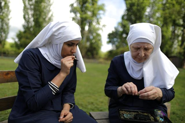 California ''weed nun'' Christine Meeusen, 57, (R), and India Delgado, who goes by the name Sister Eevee, smoke a joint at Sisters of the Valley near Merced, California. REUTERS/Lucy Nicholson