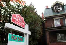 """FILE PHOTO --  A """"Sold over asking"""" sign is on display on a house for sale in Toronto's housing market in Toronto, Ontario, Canada, October 21, 2016.  REUTERS/Hyungwon Kang/File Phot"""