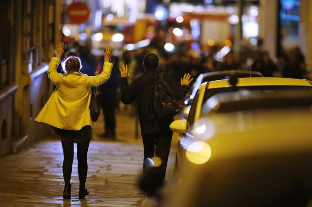 People raise their arms to show their hands as they walk towards police on a side road near the Champs Elysees  Avenue after shooting incident in Paris, France, April 20, 2017. REUTERS/Benoit Tessier