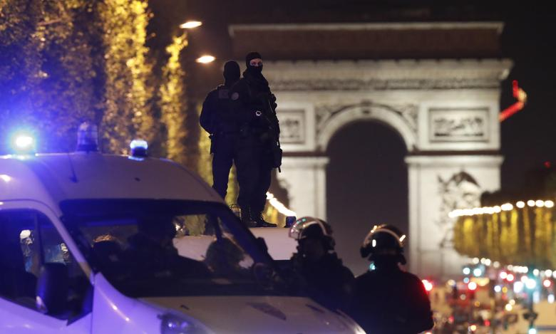 Masked police stand on top of their vehicle on the Champs Elysees Avenue after two policemen were killed and another wounded in a shooting incident in Paris, France, April 20, 2017. REUTERS/Christian Hartmann