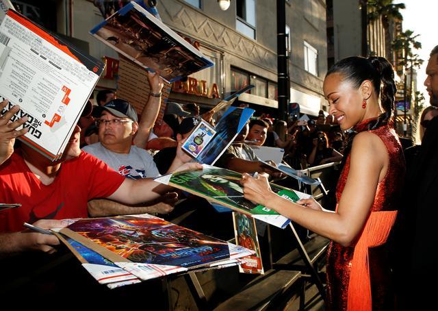 Actor Zoe Saldana signs autographs. REUTERS/Danny Moloshok