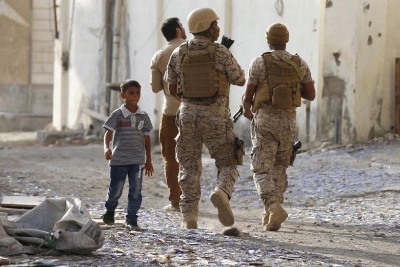 A boy walks past soldiers from the Saudi-led coalition patrolling a street in Yemen's southern port city of Aden September 26, 2015.  REUTERS/Faisal Al Nasser