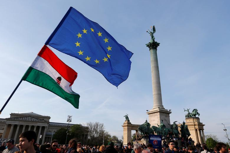 FILE PHOTO: People wave Hungarian and European Union flags as they protest in Heroes' square against a new law that would undermine Central European University, a liberal graduate school of social sciences founded by U.S. financier George Soros, in Budapest, Hungary April 12, 2017. REUTERS/Laszlo Balogh