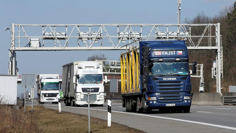 FILE PHOTO: Trucks pass through an electronic toll gate on the A10 highway south of Berlin February 26, 2015. REUTERS/Fabrizio Bensch/File Photo