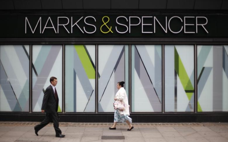 Pedestrians walk past an M&S shop in northwest London July 8, 2014.  REUTERS/Suzanne Plunkett/File photo