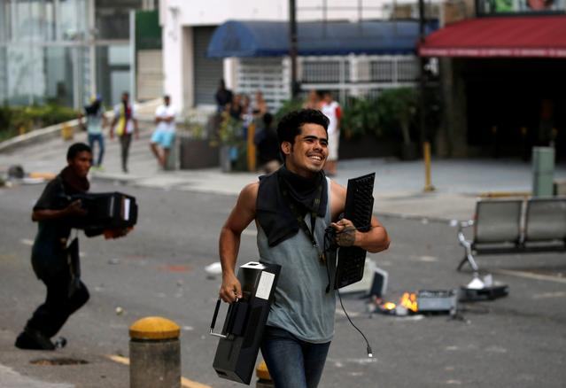 People run with looted items from an office building during the so called ''mother of all marches'' against Venezuela's President Nicolas Maduro in Caracas, Venezuela, April 19, 2017. REUTERS/Carlos Garcia Rawlins