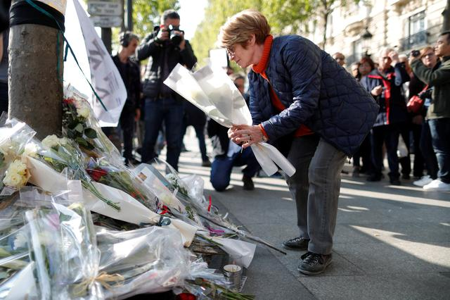 A woman leaves flowers on the Champs Elysees Avenue the day after a policeman was killed and two others were wounded in a shooting incident in Paris, France, April 21, 2017. REUTERS/Charles Platiau