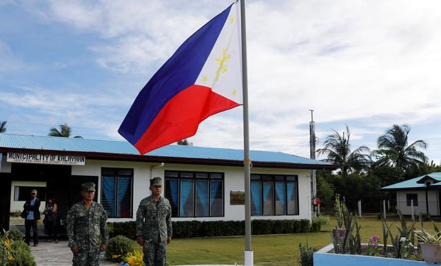 Filipino soldiers stand at attention near a Philippine flag at Thitu island in disputed South China Sea April 21, 2017. REUTERS/Erik De Castro