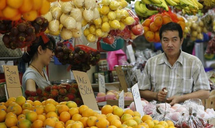 Market traders wait for customers at a fruit stall in Singapore June 23, 2008. REUTERS/Rob Dawson/Files