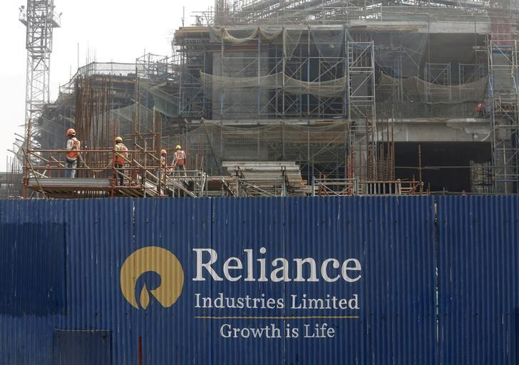 Labourers work behind an advertisement of Reliance Industries Limited at a construction site in Mumbai, India, March 2, 2016.   REUTERS/Shailesh Andrade/File Photo