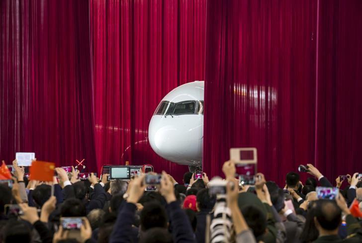 People take pictures and videos as the first C919 passenger jet made by the Commercial Aircraft Corp of China (Comac) is pulled out from behind a curtain during a news conference at the company's factory in Shanghai, November 2, 2015.   REUTERS/China Daily/File Photo