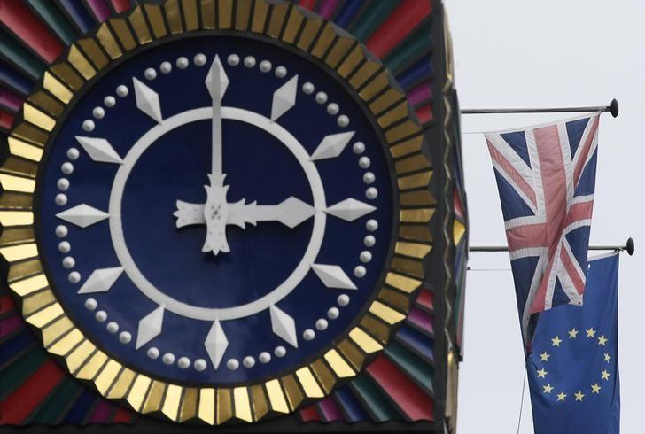The British Union flag and the European Union flag are seen flying behind a clock in the City of London, Britain, January 16 , 2017. REUTERS/Toby Melville/Files