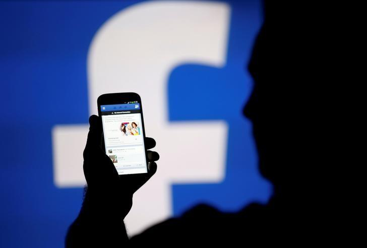 A man is silhouetted against a video screen with a Facebook logo as he poses with a Samsung S4 smartphone in this photo illustration August 14, 2013. REUTERS/Dado Ruvic/File Photo