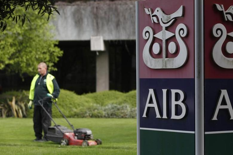 FILE PHOTO - A gardener mows the grass outside the headquarters of AIB in Dublin April 12, 2011.  REUTERS/Cathal McNaughton
