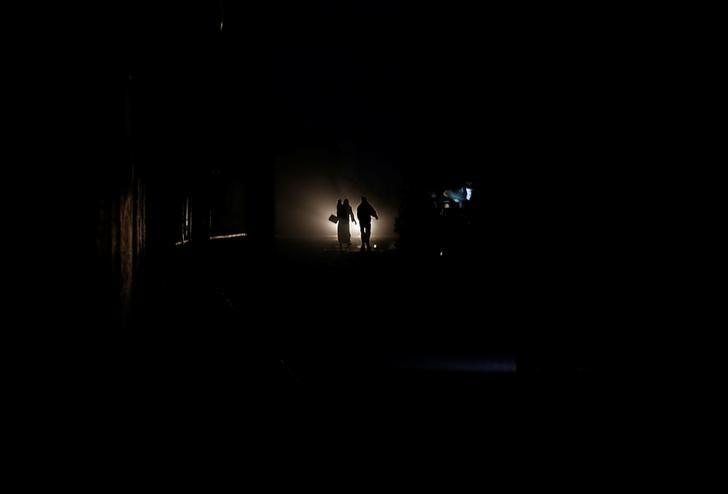 Palestinians walk on a road during a power cut in Beit Lahiya in the northern Gaza Strip January 11, 2017.REUTERS/Mohammed Salem/Files