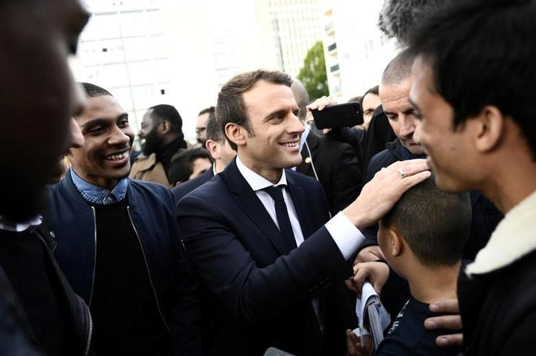 Emmanuel Macron (C), head of the political movement En Marche !, or Onwards !, and candidate for the 2017 presidential election, speaks with youths during a campaign visit in Sarcelles, near Paris, April 27, 2017.  REUTERS/Martin Bureau