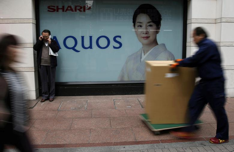 FILE PHOTO: People walk past an advertisement for Sharp Corp's Aquos television outside an electronics retail store in Tokyo, Japan, March 30, 2016. REUTERS/Yuya Shino/File Photo