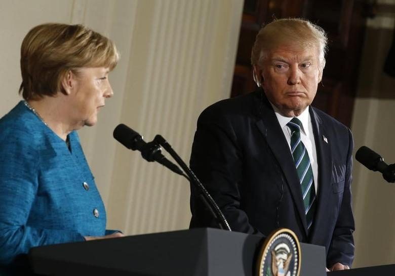 Germany's Chancellor Angela Merkel speaks as U.S. President Donald Trump looks on during their joint news conference in the East Room of the White House in Washington, U.S., March 17, 2017. REUTERS/Joshua Roberts