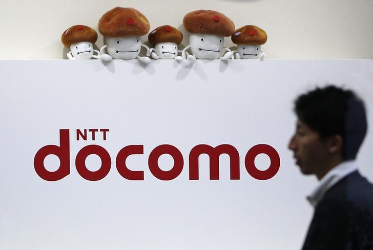 A man walks past the logo of Japan's biggest mobile phone operator NTT Docomo at its shop in Tokyo July 3, 2013.  REUTERS/Issei Kato/Files