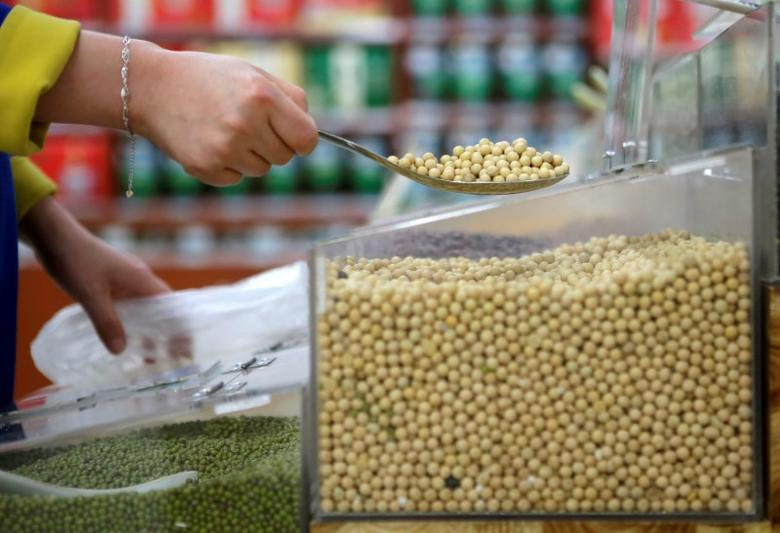 FILE PHOTO: A customer scoops soybeans as she shops at a supermarket in Wuhan, Hubei province April 14, 2014. REUTERS/Stringer/File Photo