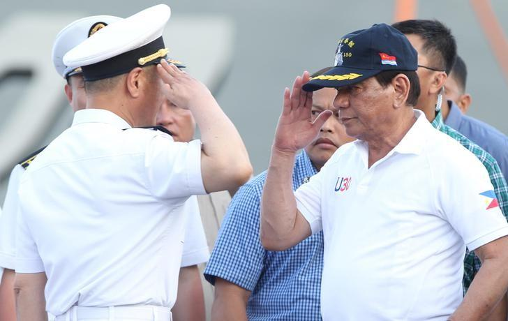 FILE PHOTO: Philippine President Rodrigo Duterte returns the salute of a Chinese Navy officer as he tours a Chinese Naval ship during a visit to Davao city, southern Philippines May 1, 2017.  REUTERS/Lean Daval Jr/File Photo