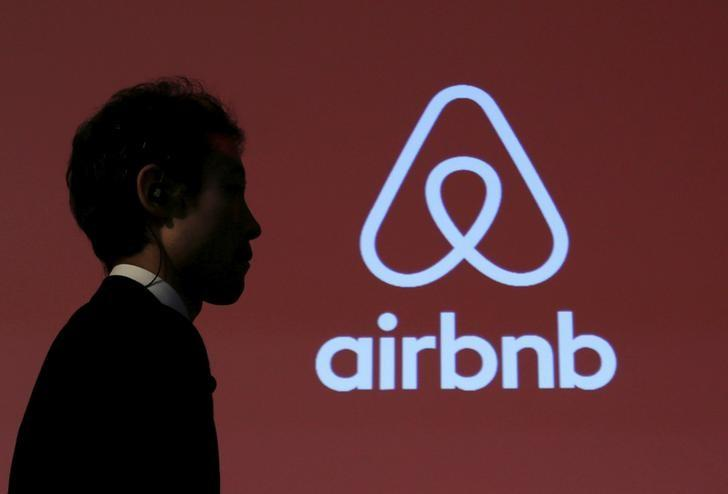 FILE PHOTO -  A man walks past a logo of Airbnb after a news conference in Tokyo, Japan, November 26, 2015. REUTERS/Yuya Shino/File Photo