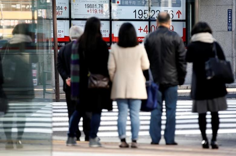 People are seen in front of an electronic board showing stock prices outside a brokerage at a business district in Tokyo, Japan, January 4, 2017. REUTERS/Kim Kyung-Hoon