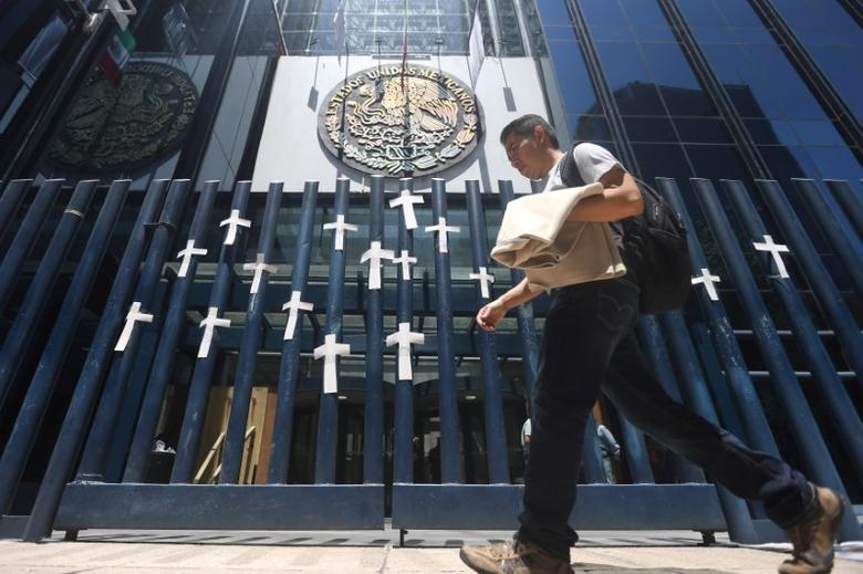 A man passes in front of crosses adhered to a fence during a protest against the murder of journalists in Mexico, outside the Attorney General's Office (PGR) in Mexico City, Mexico, April 1, 2017. REUTERS/Edgard Garrido