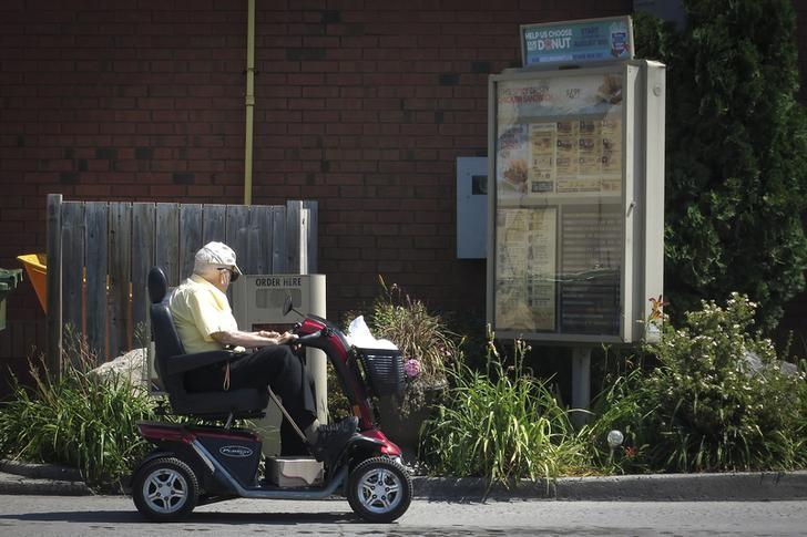 REPRESENTATIVE IMAGE: A man on a wheel scooter places an order at a Tim Hortons drive-thru restaurant in Bobcaygeon, Ontario August 9, 2014.        REUTERS/Carlo Allegri/File Photo