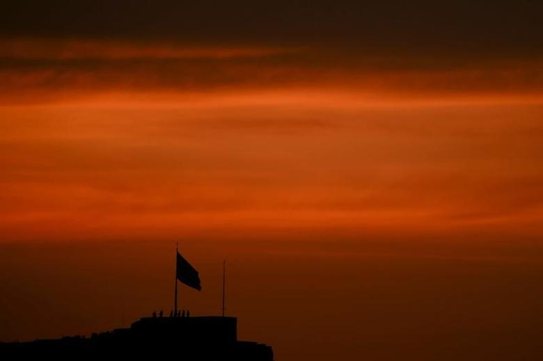 Greek soldiers are silhouetted during a ceremony to bring down the national flag atop the Acropolis hill during sunset in Athens, Greece, April 11, 2017. REUTERS/Alkis Konstantinidis