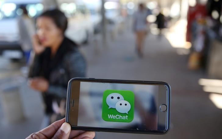 FILE PHOTO - A WeChat logo is displayed on a mobile phone as a woman walks past as she talks on her mobile phone at a taxi rank in this picture illustration taken July 21, 2016. REUTERS/Siphiwe Sibeko/Illustration/File Photo