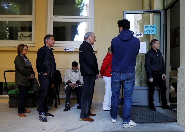 People wait in line before the opening of a polling station for the second round of 2017 French presidential election at a polling station in Marseille, France, May 7, 2017.  REUTERS/Philippe Laurenson