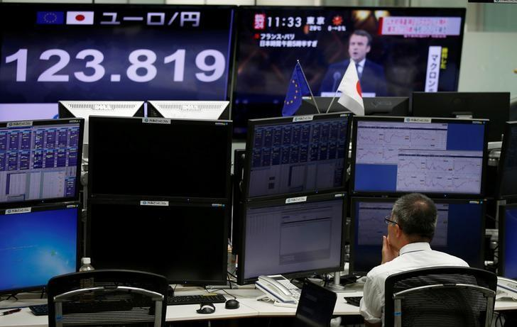 An employee of a foreign exchange trading company works near monitors showing French President-elect Emmanuel Macron (top R) on TV news and the Japanese yen's exchange rate against the euro in Tokyo, Japan, May 8, 2017.  REUTERS/Toru Hanai