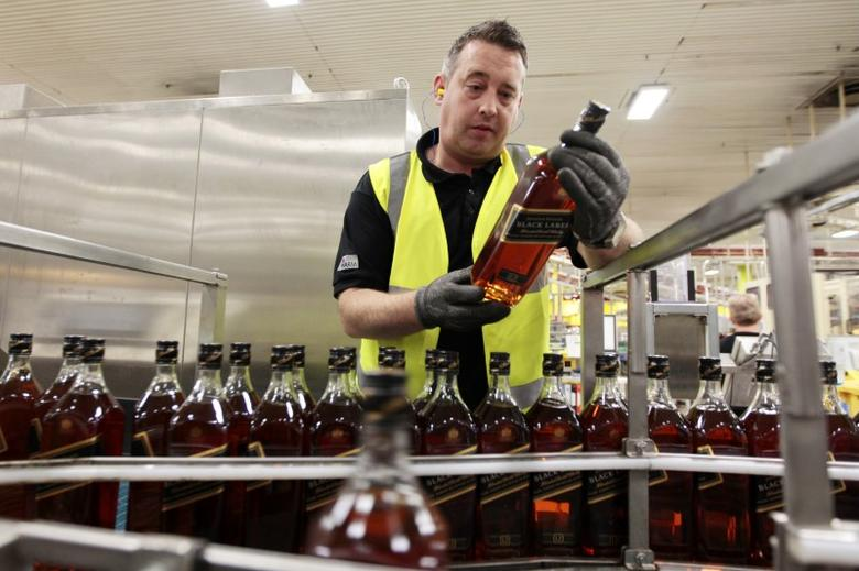 FILE PHOTO: A worker looks at bottles of Johnnie Walker whisky on the production line at the Diageo owned Shieldhall bottling plant in Glasgow, Scotland, in this March 24, 2011 file photo.  REUTERS/David Moir