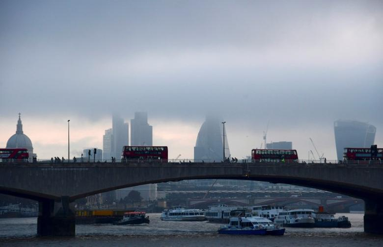FILE PHOTO: City workers cross the River Thames with the City of London financial district seen behind them, in Britain October 27, 2016. REUTERS/Toby Melville/File Photo
