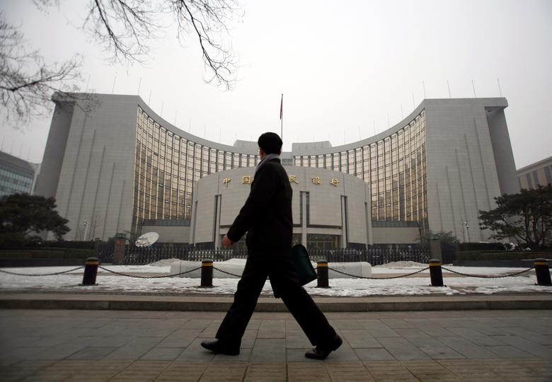 FILE PHOTO: A man walks past the headquarters of the central bank of the People's Republic of China in Beijing, January 19, 2010.  REUTERS/Loic Hofstedt/File Photo