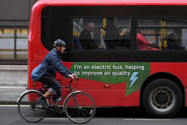 FILE PHOTO: A cyclist rides past an electric public bus on the day that Mayor of London Sadiq Khan outlined plans to place a levy on the most polluting vehicles in London, Britain, April 4, 2017.  REUTERS/Toby Melville