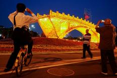 "People take pictures of the ""Golden Bridge on Silk Road"" installation by artist Shuyong, set up ahead of the Belt and Road Forum in Beijing, China May 10, 2017. REUTERS/Thomas Peter"