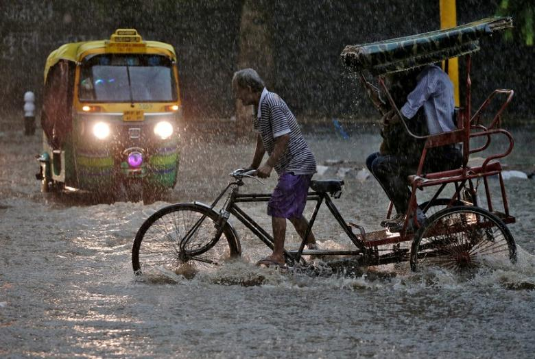 FILE PHOTO: A man pedals his cycle rickshaw during monsoon rains in New Delhi, India August 31, 2016. REUTERS/Cathal McNaughton/File Photo