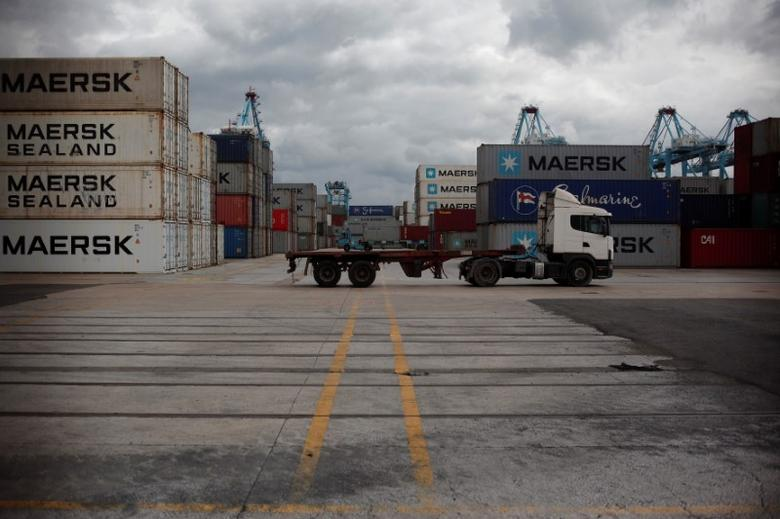 Truck drivers drive between containers in a cargo terminal at the port of Algeciras, southern Spain, March 3, 2017.  REUTERS/Jon Nazca