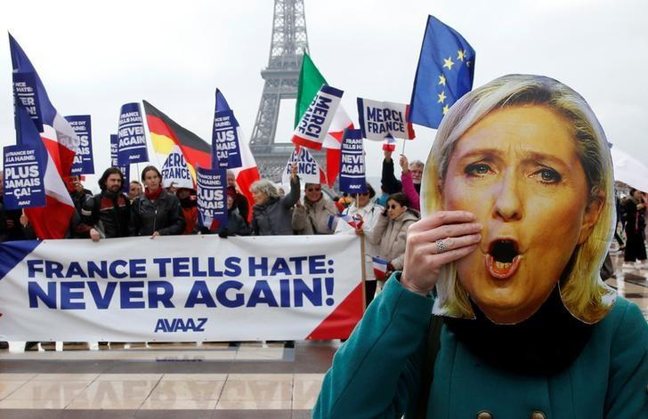 A person holds a mask of France's National Front (FN) defeated presidential candidate, Marine Le Pen, as people gather with French and European flags near the Eiffel Tower and a banner with the message, ''France tells Hate: Never Again'' the day after presidential elections in the country, in Paris, France, May 8, 2017.  REUTER/Pascal Rossignol