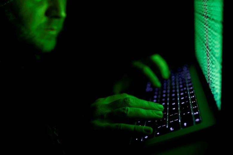 FILE PHOTO: A man types on a computer keyboard in front of the displayed cyber code in this illustration picture taken March 1, 2017. REUTERS/Kacper Pempel/Illustration/File Photo