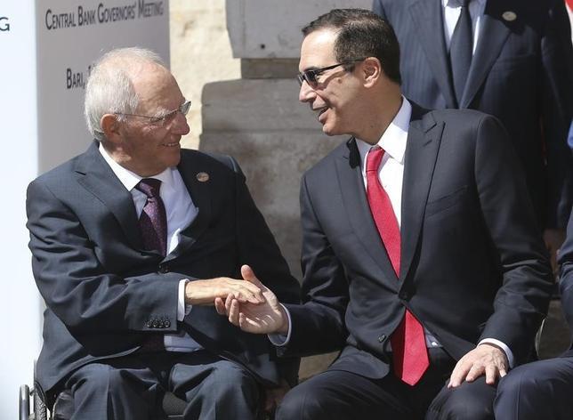 5月13日、G7財務相・中央銀行総裁会議は、サイバー犯罪に対する連携強化や通貨安競争の回避などを盛り込んだ共同声明を採択、閉幕した。写真は、握手するショイブレ独財務相(左)とムニューシン米財務長官(2017年 ロイター/Alessandro Bianchi)