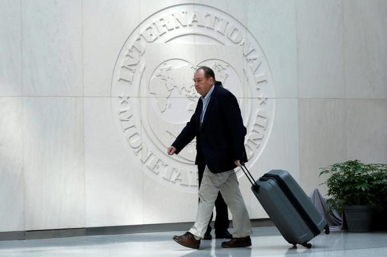 A man walks past the International Monetary Fund logo during the IMF/World Bank spring meetings in Washington, U.S., April 21, 2017. REUTERS/Yuri Gripas/Files