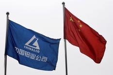 FILE PHOTO: An Aluminium Corp of China (Chinalco) company flag and the Chinese national flag are seen outside its headquarters in Beijing, China March 19, 2010. REUTERS/Christina Hu/File Photo