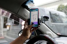 FILE PHOTO: Maya Jackson, a Lyft driver from Sacramento, responds to a ride request on her smartphone during a photo opportunity in San Francisco, California February 3, 2016.  REUTERS/Stephen Lam/File Photo