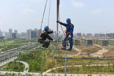 Labourers work on an electricity transmission tower in Chuzhou, Anhui province, China, May 16, 2017. REUTERS/Stringer